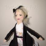 DZIECKO-lalka 01-Laleczka szyta z bawełny ubrana w białą sukienkę w kolorowe kwiatki, brązowy sweterek, kozaczki i opaskę. Twarz malowana, włosy wełniane-01